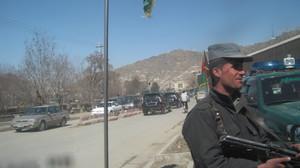 Kuvassa on autotie ja sen varrelle seisoo autonsa pysäköinyt mies kivääri kädessään.  foto: Minna Sirnö, Kabul, 2011