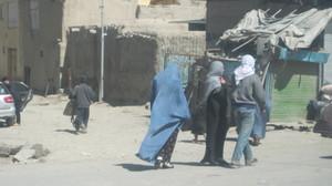 Kuvassa on naisia ja miehiä raunioituneen Kabulin kaduilla.
