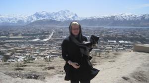 Kuvassa olen minä Kabulin esikaupungin liepeillä. Taustallani näkyy esikaupunkia ja lumihuippuisia vuoria.