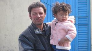 Kuvassa on isä pieni tytär sylissään.  foto: Minna Sirnö, Kabul, 2011