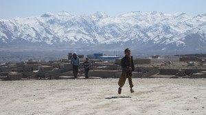 Kuvassa kolme pikkupoikaa on nousemassa Kabulin esikaupungista kohti vuoristoa.  foto: Minna Sirnö, Kabul, 2011